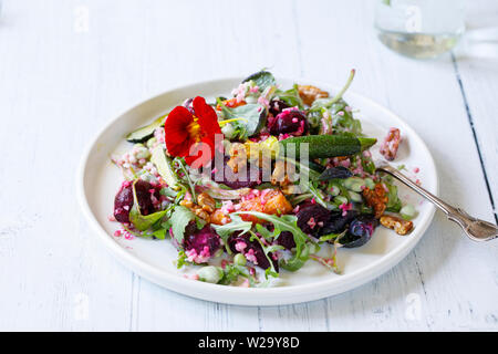 Bulgur wheat salad with roast beetroots, carrots, zucchini and green peas - Stock Image
