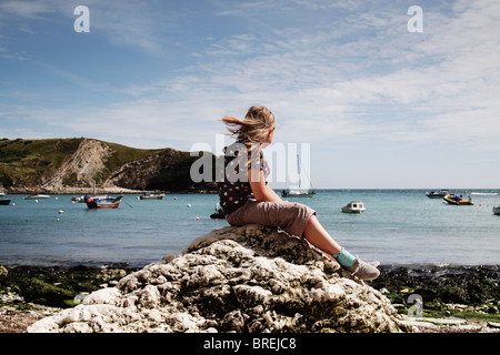 girl sitting on a rock at Lulworth Cove,UK - Stock Image