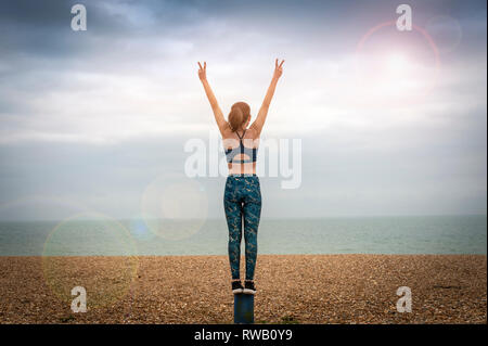 woman standing with arms raised on beach, back view, copyspace, lens flare - Stock Image