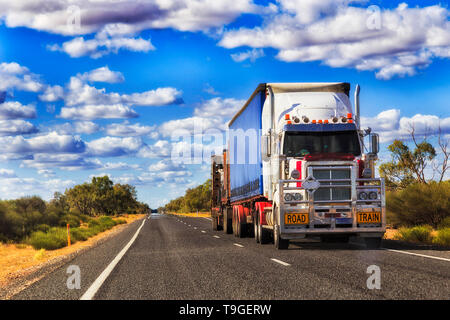 Long mighty road train truck moving cargo across Australia on a remote lonely empty outback highway in rural NSW. - Stock Image