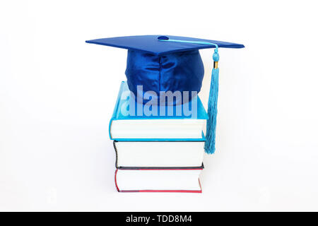 Blue graduation cap on top of books isolated on white background. Education concept. - Stock Image