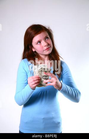 Girl holding US dollar bills - Stock Image