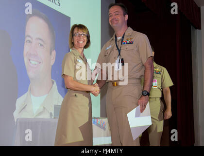 180829-N-NR803-003 – NMCP recognized ten master clinicians and ten associate master clinicians in a ceremony held in the medical center's auditorium, Aug. 28. Capt. Carolyn Rice, NMCP acting commanding officer (left) with Cmdr. Tom Douglas, one of the new master clinicians. - Stock Image