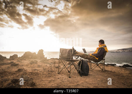 Travel and enjoying outdoor people concept with lonely man working on laptop internet connecetd computer sitting in front of an amazing sunset on the  - Stock Image