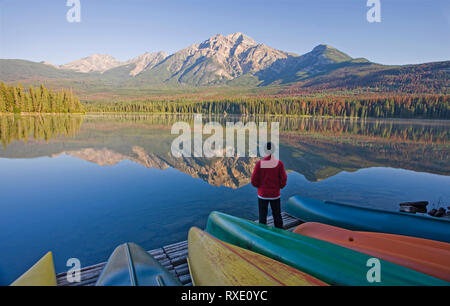 Lone middle age male standing on dock with canoes looking at Pyramid Mountain at Pyramid Lake, Jasper National Park, Alberta, Canada - Stock Image