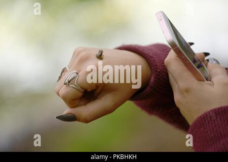 Girl photographing a young frog, Rana temporaria on the back of her hand using an iphone smartphone digital camera, Wales, UK. Wales, UK. - Stock Image