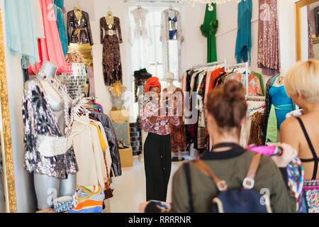 Young women friends with camera phone shopping in clothing store - Stock Image