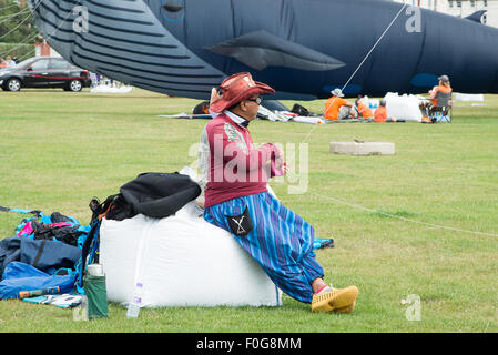 Portsmouth, UK. 15th August 2015. A kite flier rests on a sand bag as he hold the line to his kite. A large whale - Stock Image