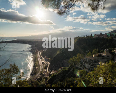 View from the town of Taormina toward Mount Etna in the distance and the seasie resort of Giardini Naxos below, Province of Messina, Sicily, Italy - Stock Image