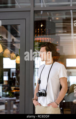 Photographer with camera around neck waiting by cafe entrance - Stock Image