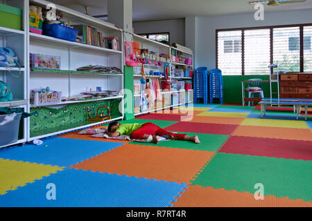 Child sleeping on the floor at a children's nursery school classroom. Thailand Southeast Asia - Stock Image