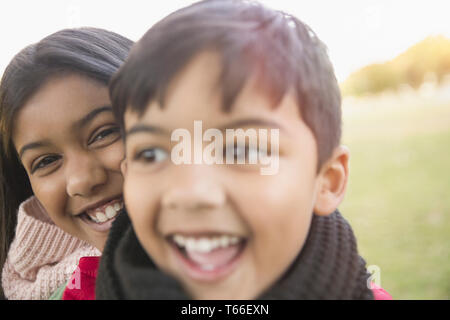 Happy brother and sister in park - Stock Image