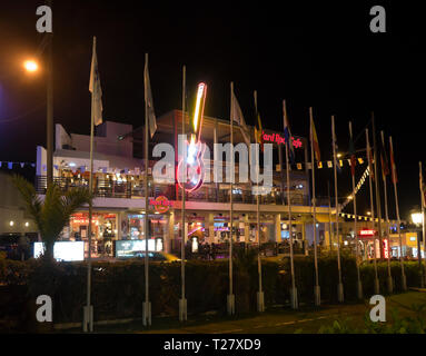 The well known guitar logo and colorful lights of the Hard Rock Cafe in Ayia Napa Cyprus - Stock Image