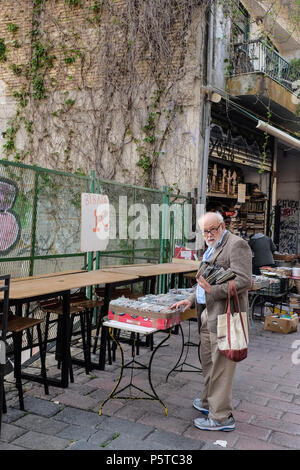 Person Man Hunting through second hand music street market sales for a bargain, Athens, Greece - Stock Image