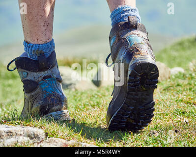A close up of a female hikers muddy walking boots on a bright sunny day - Stock Image