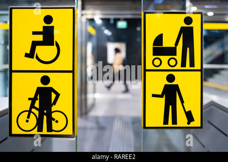 handicapped, bicycle, stroller and big luggage yellow pictrogram in metro, information in public transport, blurred person in the background - Stock Image