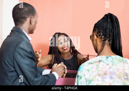 The smiling businesswoman speaks to her customers. - Stock Image