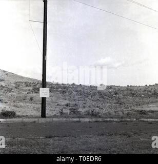 1950s, Rabies notice on telegraph pole, Uganda, Africa. Notice reads 'Rabies Control. Poison Area. Obutwa, Sumu. - Stock Image