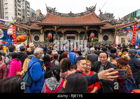 Taipei, Taiwan, Feb. 5, 2019: Two visitors take a selfie as they enter Longshan Temple in Taipei on Tuesday, Lunar New Year's Day, to pray and welcome the arrival of the Year of the Pig. Credit: Perry Svensson/Alamy Live News - Stock Image
