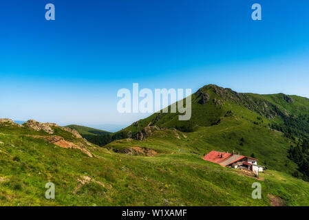 Idyllic landscape in the Old mountain, Central Balkan national park in Bulgaria. Eho hut surrounded with fresh green mountain pastures with flowers - Stock Image