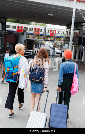 Young women friends with suitcases outside urban train station - Stock Image