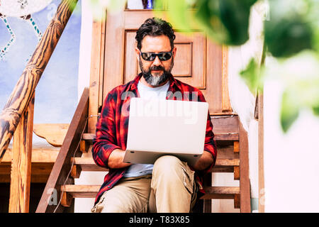 People and computer outdoor - free professional man work outside home with internet connection and notebook sitting on a wooden stair - alternative op - Stock Image