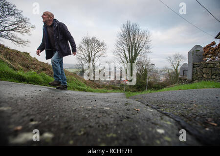 A man walking up Ffordd Pen Llech, Harlech, Gwynedd, which local residents re claiming to be  the steepest street in the world, and have put in a bid for this statuus with the Guiness Book of Records  The steepest 10-metre section [the crucial distance for the world record] is 39.25%  January 2019 - Stock Image