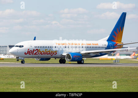 A Jet2 Holiday Boeing 737-800, registration G-JZBO, preparing for take off from Manchester Airport, England. - Stock Image