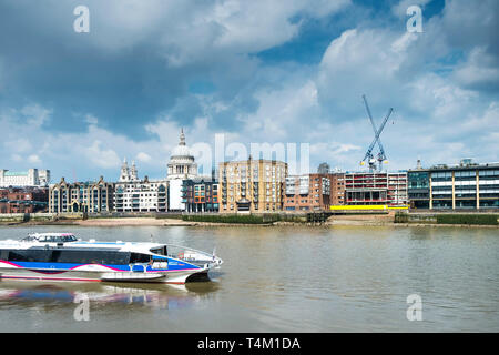 A Thames Clipper River Boat on the River Thames with the dome of St Pauls Cathedral in the background. - Stock Image