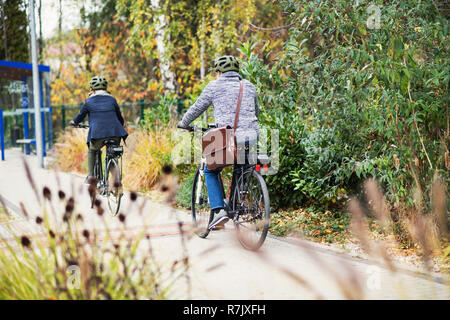 A rear view of active senior couple with helmets and electrobikes cycling outdoors on a pathway in town. - Stock Image