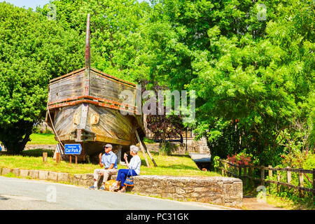 11 June 2018: Charlestown, Cornwall, UK - Greek Trireme Nomos, built for the film Clash of the Titans, and a senior couple eating ice cream in front o - Stock Image