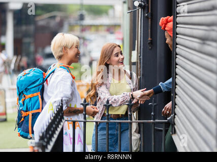 Young women friends with backpack arriving at urban house rental - Stock Image
