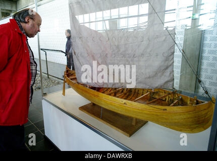 A visitor takes a look at a model of a Viking ship of the 11th century, discoverd in the Roskilde fjord in 1962, - Stock Image