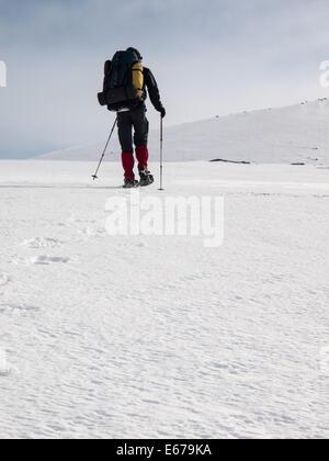 Man with heavy backpack snowshoeing in winter mountain landscape. Huldraheimen, Gausdal Westfjel, Norway - Stock Image