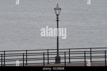 An antique lamppost and railings on a dull, grey, cloudy day on the promenade at Southsea. Southsea. Portsmouth, Hampshire, UK. - Stock Image