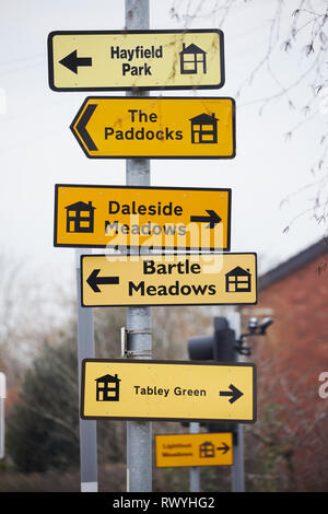 many new build Building housing estate yellow show homes direction signs tied to lampposts on the roadside in Lancashire. - Stock Image