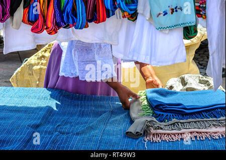 Fabric or cloth vendor in the main marketplace of Otavalo Ecuador - Stock Image