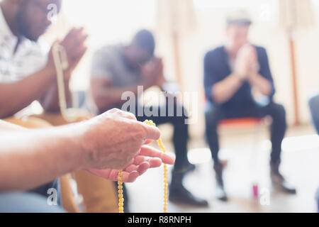 Men praying with rosaries in prayer group - Stock Image