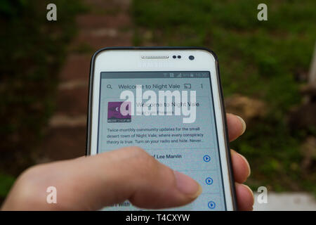 A smartphone with 'Welcome to Night Vale' podcast playing, outdoors - Stock Image