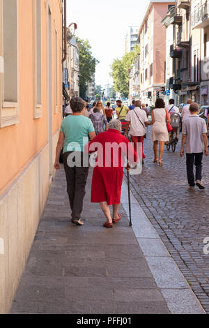 People of different generations walking in the quiet streets after church including elderly lady in a red coat, Sunday morning, Piacenza, Italy - Stock Image