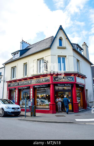 The boulanger and patissier in Carantec, Brittany, France sells their bread and pastries from a bright-coloured corner shop. - Stock Image