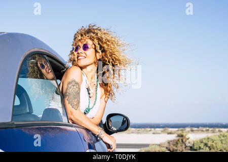 Beautiful cheerful happy caucasian woman outside the car with wind in curly long blonde hair - attractive people enjoying the freedom in outdoor coast - Stock Image