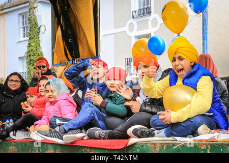 Gravesend, Kent, UK, 13th April 2019. Children wave and smile from a float. Thousands of spectators and religious visitors line the streets of Gravesend in Kent to watch and participate in the annual Vaisakhi procession. Vaisakhi is celebrated by the Sikh community all over the world. - Stock Image