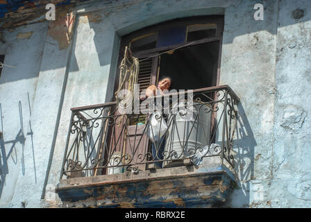 Cuban woman standing on the balcony and smiling at the camera - Stock Image