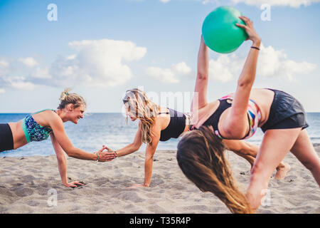 Yoga fitness and pilates sport activity with three young beautiful girl outdoor at the beach enjoying the healthy lifestyle together - fit people and  - Stock Image