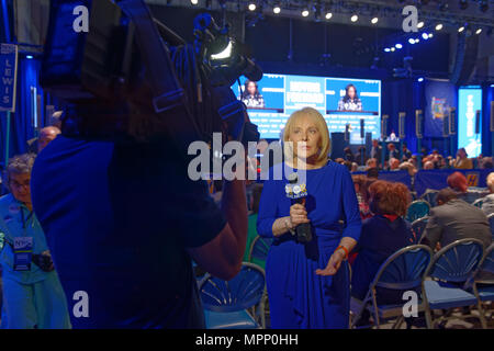 Long Island, USA. 23rd May, 2018. MARCIA KRAMER, WLNY 10/55 Political Reporter, tapes news segment with audience and stage in background during Day 1 of New York State Democratic Convention, held at Hofstra University on Long Island. Credit: Ann E Parry/Alamy Live News - Stock Image