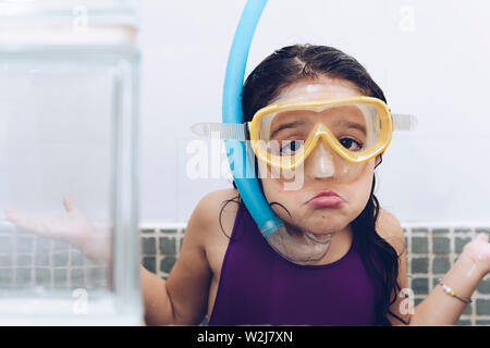 portrait of a funny pretty little girl grimacing with snorkel goggles in the tub while taking a bath in the bathtub, kids hygiene concept, copy space - Stock Image