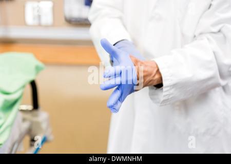 Doctor Wearing Sterilized Gloves In Hospital - Stock Image