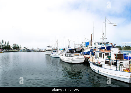Boats for pleasure and commercial fishing work sit side by side in the harbour at Lakes Entrance in Victoria, Australia. - Stock Image