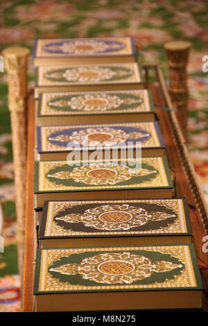A line of holy Qurans in different cover designs at the grand mosque - Stock Image